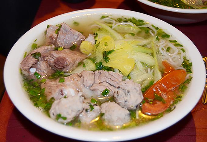 Bún sườn chua  Với vị chua thanh của nước dùng và nhiều loại rau, thịt bên trong, bún sườn chua từ lâu là món ăn hấp dẫn du khách ở Hà Nội. Bên trong một bát bún có thịt lợn luộc thái mỏng, lưỡi lợn, sườn, thịt mọc kèm theo dứa tươi, cà chua, dọc mùng và thứ nước lèo chua chua lại ngọt vị nước hầm xương. Từng viên mọc giòn giòn làm từ thịt xay cùng nấm hương, mộc nhĩ khiến món ăn thêm đa dạng hương vị.  Gợi ý địa chỉ: 181 Xã Đàn, 2 Phạm Ngọc Thạch, 251 phố Vọng, 71/14 Hoàng Văn Thái. Giá: 40.000 - 55.000 đồng một bát. Ảnh: Nguyên Chi.