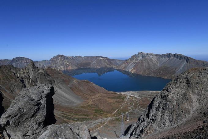 Vùng núi Paektu được cho là nơi các lãnh đạo Triều Tiên chào đời. Đây là đỉnh núi cao nhất bán đảo Triều Tiên với 2.744 m so với mực nước biển. Ngọn núi này cũng xuất hiện trong bức khảm phía sau tượng hai cố lãnh đạo của Triều Tiên (hình 1). Nhiều người Hàn Quốc thường xuyên lên núi Paektu, nhưng từ phía Trung Quốc. Moon Jae-in là tổng thống Hàn Quốc tại nhiệm đầu tiên tới thăm núi Paektu trên lãnh thổ Triều Tiên trong hội nghị liên Triều lần ba. Ảnh: Reuters.
