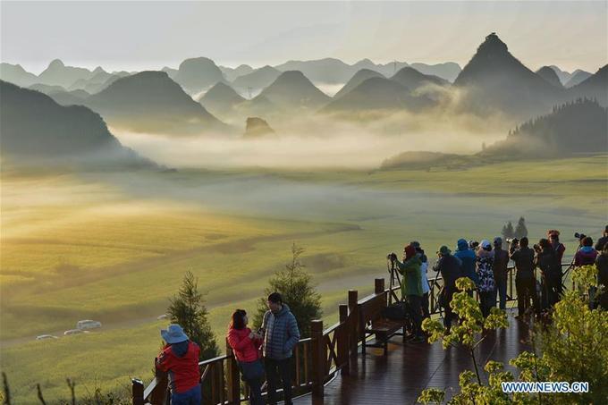 """Làn sương khói mờ ảo, quấn quýt lấy những ngọn đồi nhấp nhô trong nắng sớm. Để chụp được khoảnh khắc này, bạn không chỉ phải dậy sớm mà còn phải """"tranh đấu"""" với những vị khách khác để có chỗ quan sát thật lý tưởng."""
