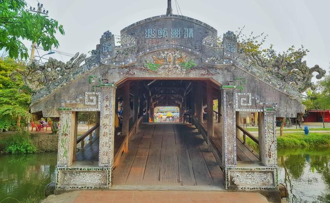 """Cầu do một người cháu gái thuộc thế hệ thứ 6 của họ Trần (một trong những dòng họ khai khẩn làng) cúng tiền để xây dựng. Công trình này làm bằng gỗ, kiến trúc theo kiểu """"thượng gia, hạ kiều"""", tức trên nhà dưới cầu, dài hơn 18 m, rộng gần 6 m."""