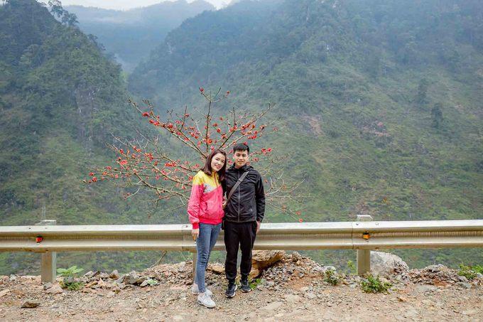 Hai bạn trẻ trong đoàn chụp ảnh bên cây hoa gạo trên đường Tráng Kìm mới mở kết nối tuyến Quản Bạ - Yên Minh.