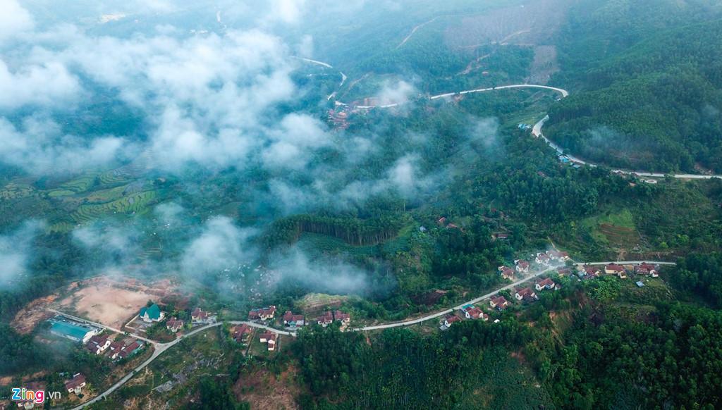 """Hai tuyến đường bên sườn núi hệt như hai """"cánh tay khổng lồ"""" ôm lấy bản làng mờ ảo giữa mây trời."""