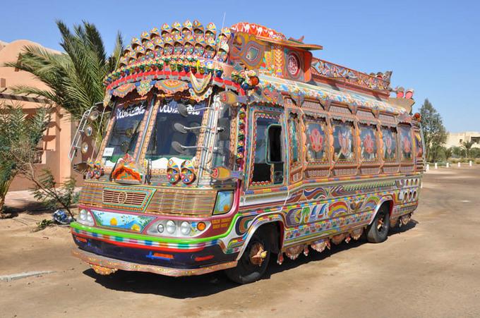 """Ngoài những chiếc xe tải, nhiều phương tiện khác ở Pakistan cũng được trang trí lộng lẫy không kém như xe bus hay xe kéo. Chiếc xe chở khách với anh chàng phụ xe trong chiếc áo truyền thống giữa hàng ngàn nét cọ nâu, vàng, đỏ, trắng trông đậm chất """"điện ảnh""""."""