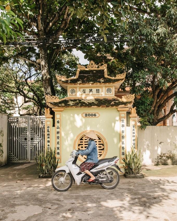 Người nông dân chạy xe máy qua một ngôi chùa ở Ninh Bình giữa trưa nắng.
