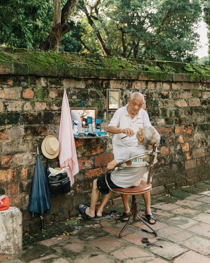 Một người thợ cắt tóc lớn tuổi đang hành nghề bên cạnh Văn Miếu (Hà Nội).