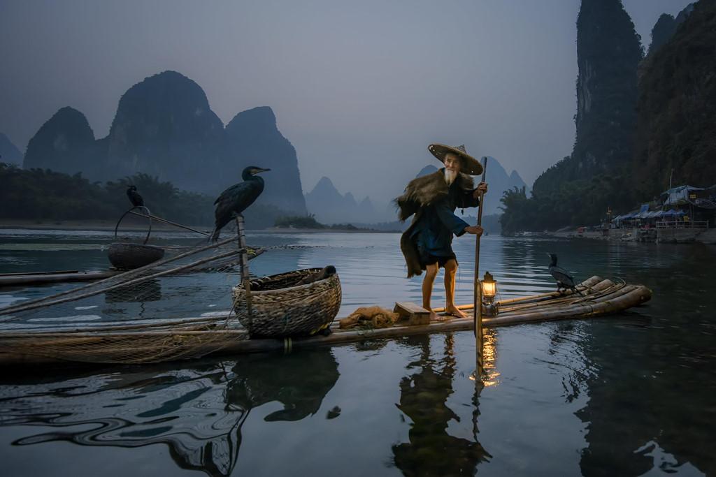 """Được mệnh danh là nơi sở hữu """"phong cảnh đệ nhất thiên hạ"""", thành phố Quế Lâm (khu tự trị dân tộc Choang Quảng Tây, Trung Quốc) sở hữu nhiều thắng cảnh thu hút hàng triệu du khách mỗi năm. Một trong số đó phải nhắc đến dòng Li Giang thơ mộng. Dọc theo con sông, du khách có thể bắt gặp cảnh tượng ngư dân địa phương bắt cá rất thú vị. Ảnh: Bobby Joshi."""