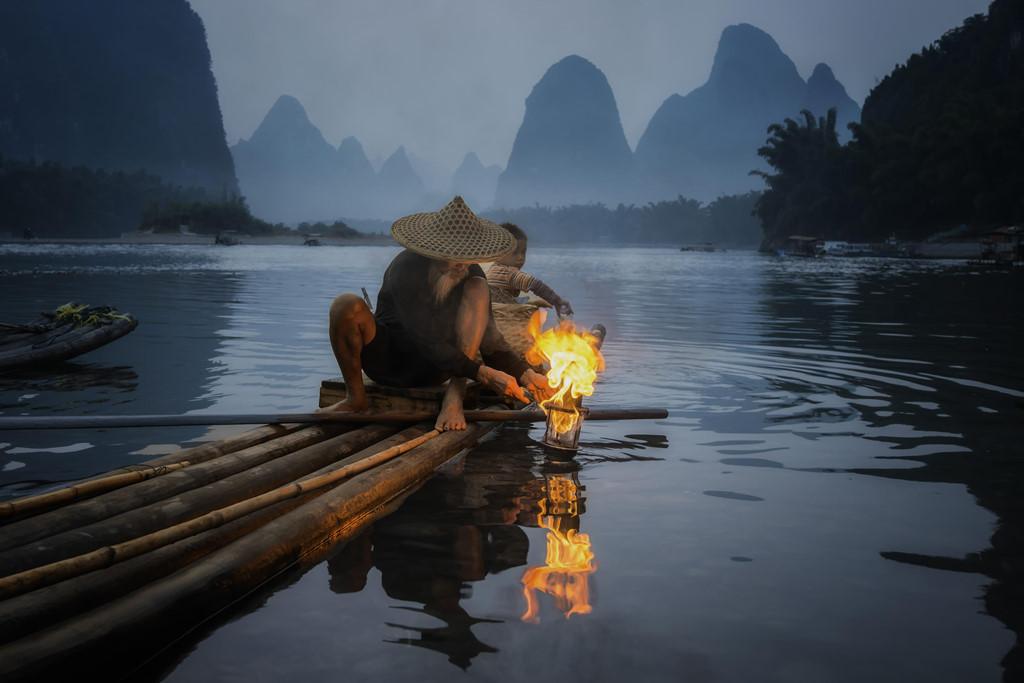 Lão ngư râu tóc bạc phơ đứng trên bè tre thô sơ, buộc dây và lưới vào cổ chim cốc rồi thả chúng xuống nước. Ảnh: Bobby Joshi.