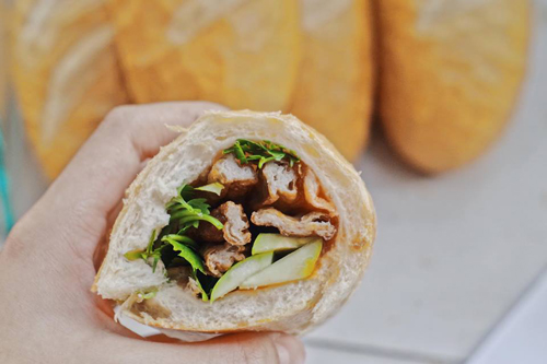 Ổ bánh mì vỏ mỏng giòn kẹp đầy ắp những thanh chả cá nóng hổi cùng các loại rau dưa.