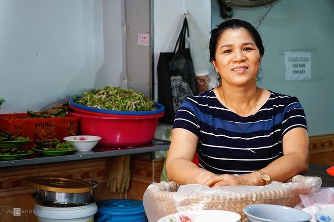 """Chị Chi năm nay 52 tuổi. Sinh ra và lớn lên trong một gia đình có truyền thống nấu nướng, ngay từ nhỏ, chị Chi đã học cách chuẩn bị các món ăn. Mở quán bún mắm cua từ năm 1998, quán của chị đã tồn tại hơn 20 năm tại phố núi. """"Lúc mới mở hàng, tôi chỉ bán ở vỉa hè. Mãi sau này mới có được không gian thoải mái cho thực khách ngồi ăn"""", bà chủ chia sẻ."""