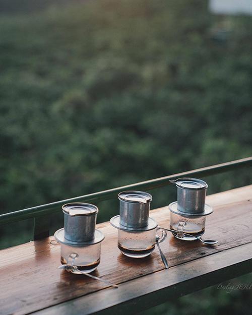 Trong màn sương giăng, bạn có thể gọi ly cà phê nóng để nhâm nhi. Bạn cũng có thể chọn các loại đồ uống khác trong thực đơn phong phú với giá trung bình 35.000 đồng.  Từ trung tâm thành phố, bạn theo hướng làng hoa Vạn Thành, rẽ tỉnh lộ ĐT725 để đi đèo Tà Nung. Men theo con đường này bạn sẽ đến nơi, trên đường là khung cảnh đồi chập chùng của miền đất cao nguyên. Ảnh: Darling Jeju.