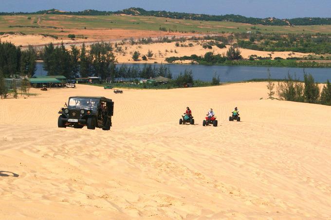 """Bàu Trắng  Bàu Trắng từng là bối cảnh cho nhiều bộ phim Việt. Nơi đây có một hồ nước, còn được du khách gọi là """"Tiểu Sahara"""" bởi những triền cát chạy dài bao quanh. Những ai yêu thích cảm giác mạnh có thể thuê xe địa hình giá khoảng 400.000 - 600.000 đồng/chiếc cho 2 người trong 20 phút. Ngoài ra, bạn có thể thả bộ quanh những triền cát, chụp ảnh hay tổ chức các trò chơi nếu đi theo nhóm. Ảnh: Hồng Hà."""