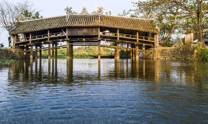 """Cầu ngói Thanh Toàn  Cầu ngói Thanh Toàn nằm ở làng Thanh Thủy Chánh, xã Thủy Thanh, thị xã Hương Thủy. Công trình này làm bằng gỗ, kiến trúc theo kiểu """"thượng gia, hạ kiều"""", tức trên nhà dưới cầu, dài hơn 18 m, rộng gần 6 m. Đây là một trong số ít cây cầu với kiểu kiến trúc này còn tồn tại đến ngày nay ở Việt Nam. Cây cầu cách trung tâm thành phố chừng 8 km. Bạn có thể đi trước để dành thời gian chiều nghỉ ngơi ở thôn Vĩ Dạ. Ảnh: Thanh Toàn."""