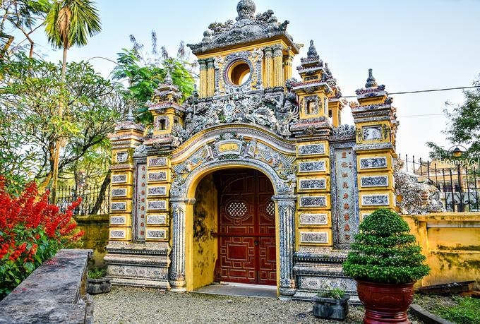 Cổng chính theo lối tam quan, gồm hai tầng, xây bằng vôi gạch và trang trí cầu kỳ bằng nghệ thuật đắp nổi sành sứ, thuỷ tinh màu. Cả hai mặt trong và ngoài của cổng đều có các hình ảnh rồng, phượng, lân, hoa lá… cùng một số văn tự và câu đối bằng chữ Hán.