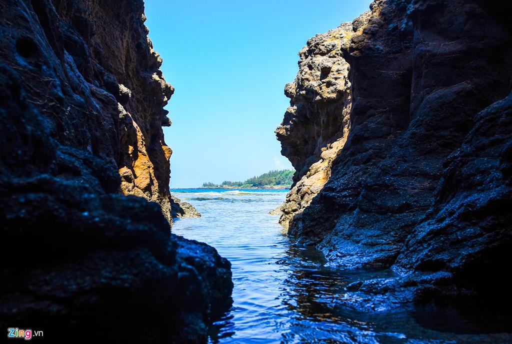 Thủy triều tràn vào khe vách đá trầm tích núi lửa phát ra nhiều âm thanh róc rách ngỡ như dòng suối tuôn trào từ trong hang núi tuôn về phía biển.