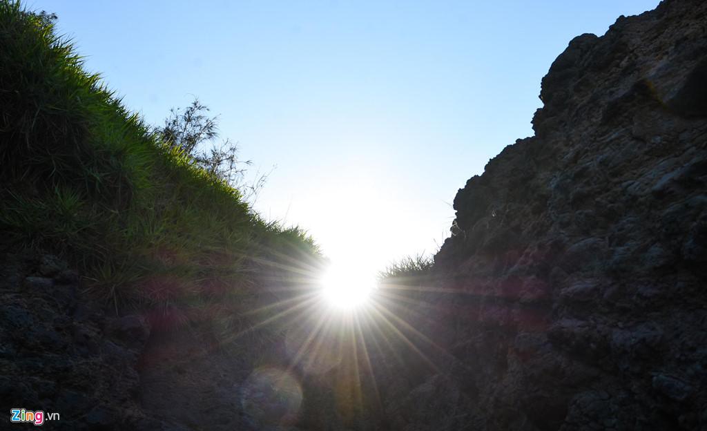 Mặt trời tỏa ánh hào quang giữa vách đá trầm tích núi lửa triệu năm.