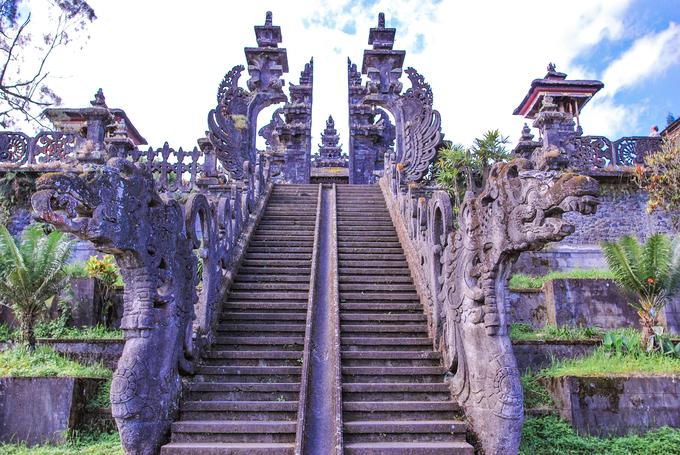 Cổng Candi Bentar là kiến trúc truyền thống của người Bali được xây dựng ở các đền thờ, nhà ở, cung điện hay nghĩa trang. Cánh cổng bao gồm hai nửa đồng dạng, đối xứng và được đặt hai bên lối vào. Khác với những kiến trúc thông thường, Candi Bentar không hề có điểm kết nối mà hoàn toàn là hai nửa tách biệt, mở ra một lối đi ở trung tâm. Ảnh: Bali Tour.