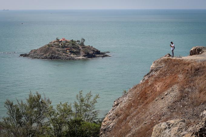 Đứng trên mô đất ven đồi, một bạn trẻ chăm chú ghi lại khung cảnh hài hòa giữa đất liền với đảo Hòn Bà giữa biển.