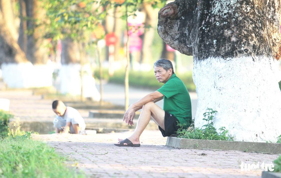 Vào những ngày hè oi ả, dọc hai bên đường, dưới bóng mát của cây xà cừ, nhiều người dừng chân nghỉ ngơi - Ảnh: DOÃN HÒA