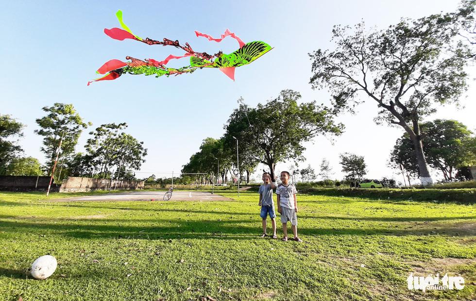 Những đứa trẻ thả diều, vui chơi bên hàng cây xanh mát - Ảnh: DOÃN HÒA