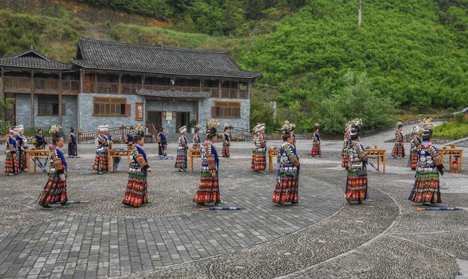 Những người phụ nữ Miêu nhảy múa theo tiếng khèn trong một buổi trình diễn văn hoá tại khoảng sân tập thể. Các sự kiện này diễn ra hàng ngày trong khắp khu Tây Giang Miêu trại để phục vụ du khách và cũng là cách để người dân duy trì văn hoá, phong tục.