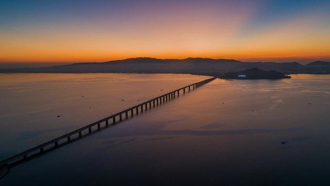 5h: Ngắm bình minh trên cầu Thị Nại  Cây cầu dài gần 7 km nối thành phố Quy Nhơn với bán đảo Phương Mai, từng là cầu vượt biển dài nhất Việt Nam. Nếu chỉ có một ngày ở Quy Nhơn, bạn nên dậy sớm để đón những ánh bình minh đầu tiên giữa biển trời rộng lớn với bầu không khí trong lành trên đầm Thị Nại. Ảnh: Trung Phạm.