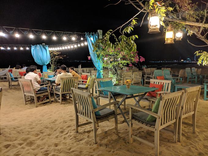 19h30: Nhâm nhi đồ uống ở Surf Bar  Nghỉ ngơi sau một ngày khám phá thành phố biển, Surf Bar là điểm đến lý tưởng tiếp theo với điểm cộng là những bộ bàn ghế gỗ đặt ngay trên nền cát, nằm trên đường ven bờ biển Xuân Diệu. Ngồi thưởng thức những món đồ uống tại quán, du khách có thể tận hưởng không gian thoáng đãng với những làn gió biển mát rượi, tiếng sóng vỗ rì rào. Một số đồ uống như cocktail, nước ép đều có giá dưới 40.000 đồng. Ảnh: Vy An.