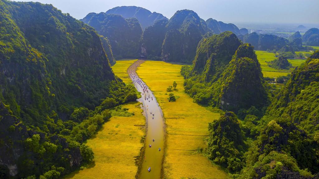 """Phải đến đây, bạn mới vỡ lẽ vì sao vùng đất này lại được mệnh danh là """"vịnh Hạ Long trên cạn"""" hay """"Nam thiên đệ nhị động"""". Nhìn từ trên cao, Tam Cốc - Bích Động đẹp như một bức tranh vẽ với sự hài hòa giữa đường nét, bố cục, màu sắc của núi, sông và những cánh đồng."""