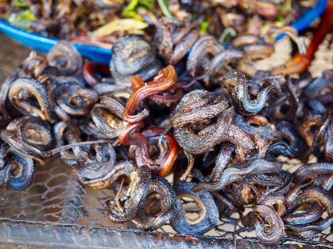 Rắn nướng  Rắn có thể chế biến thành các món như nấu cháo đậu xanh, hầm đu đủ, xào lăn... nhưng bạn dễ dàng tìm thấy khi đến Campuchia là món nướng. Những con rắn đủ mọi kích cỡ được làm sạch rồi nướng mọi dân dã. Món ăn này cũng phổ biến ở Việt Nam. Tại một số địa chỉ ở Siem Reap hoặc Phnom Penh, mỗi con rắn được bán với giá 2 USD (hơn 40.000 đồng). Người bán còn làm ra nhiều loại nước chấm khác nhau để phục vụ khách. Ảnh: Freda Bouskoutas.