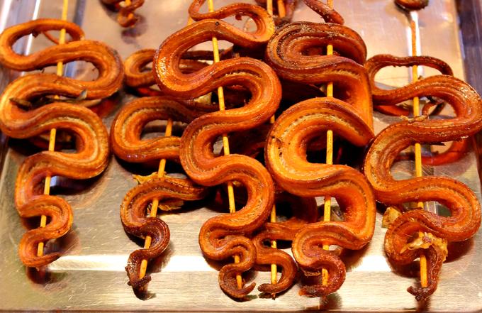 Riêng tại các chợ đông khách du lịch ở Phnom Penh, người dân chế biến rắn chiên thay vì nướng. Thoạt nhìn, những xiên rắn nằm ngửa khiến bạn cảm thấy rùng mình, nhưng mùi thơm và lớp da giòn bên ngoài sẽ khiến bạn nhớ món này. Ảnh: Al Geba.