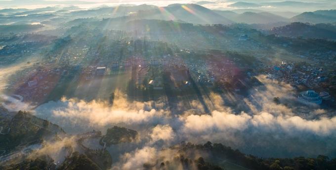 """Theo nhiếp ảnh gia Trần Quang Anh, từ 5h30 đến 6h30 hàng ngày là thời gian """"săn"""" ảnh bình minh đẹp nhất. Khi đó, mây trôi la đà qua trung tâm thành phố, đồi núi, hồ nước và rừng thông, tạo nên khung cảnh đẹp như trong cổ tích."""