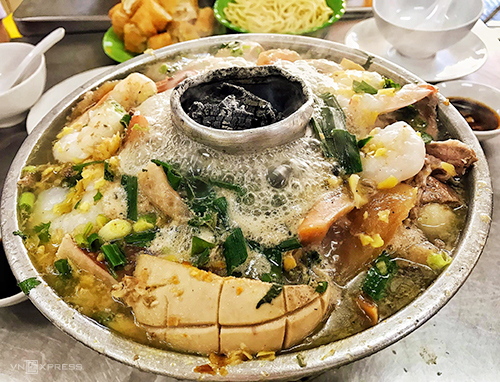 Lẩu Dân Ích  Nồi lẩu sôi sùng sục, nghi ngút khói luôn là lựa chọn lý tưởng vào mùa mưa. Nằm ở khu người Hoa, trên đường Châu Văn Liêm, quận 5 là quán lẩu lâu năm. Đây là một trong những địa chỉ ăn uống về đêm đông khách bậc nhất ở khu này. Lẩu ở đây được nấu theo kiểu của người Hoa với nồi nhôm được đốt than hồng ở giữa. Bạn có thể chọn các loại lẩu cá, lẩu hải sản nhưng lẩu thập cẩm là suất ăn được nhiều người gọi nhất. Giá theo kích cỡ: 250.000 - 320.000 - 420.000 đồng. Bên trong nồi lẩu thập cẩm có cá, tôm, mực, chả cá, cá viên, cật... và các loại rau ăn cùng như rau cải, tần ô, cải chua. Nước lẩu có độ trong, hơi ngọt và ít béo. Bên cạnh món chính là lẩu, bạn có thể gọi thêm nhiều món ăn khác trong thực đơn đa dạng như: cơm chiên cá mặn, cua rang muối, đậu hủ xào thập cẩm, chân vịt xào cải chua, nấm đông cô nhồi tôm... với giá trung bình 70.000 đồng một đĩa.