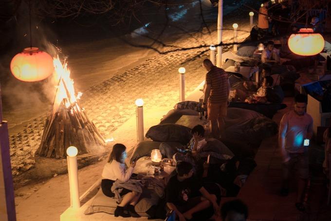 Khu ngồi sát bờ biển lúc này trở nên lãng mạn dưới ánh đèn lung linh. Dù quán khá đông nhưng vẫn có đủ góc riêng tư dành cho bạn. Khi thủy triều thấp, khách Tây thường xuống tận bãi cát ngồi ngắm biển đêm.