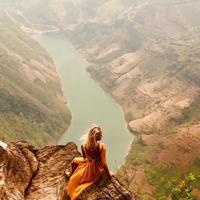 """Để có thể ngắm sông Nho Quế ở vị trí thuận lợi nhất, các du khách thường chọn dừng chân ở đèo Mã Pí Lèng. Dù phải chạy qua con đường dài 20 km hiểm trở, nhiều người vẫn rất thích đến đây để tận hưởng cảnh đẹp của dòng sông và chụp những tấm hình thật """"chất"""" ở những mỏm đá lớn. Ảnh: lolaoome."""