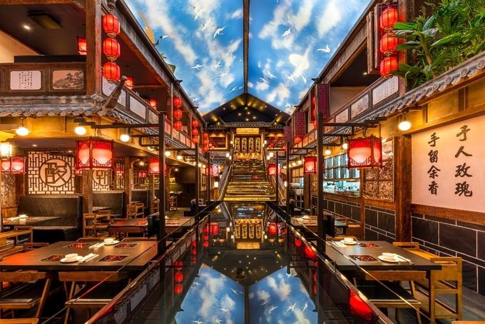 """Đặt chân vào bên trong, thực khách lạc vào không gian đậm chất Trung Hoa ngay giữa lòng Sydney. Thiết kế của quán tựa như """"tửu lầu"""" (quán rượu) xưa ở Trung Quốc, đèn lồng đỏ treo cao, bàn ghế gỗ kiểu đơn giản. Hồ nước ngay chính giữa tạo cho bạn cảm giác như đang ngồi ăn lẩu tại một thủy trấn."""