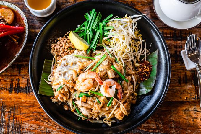 """Pad Thai (phở xào)  Pad Thai từ lâu là """"món ăn quốc gia"""" của Thái Lan, ra đời trong thời điểm đất nước này gặp khó khăn, khi người dân phải trộn tất cả nguyên liệu có sẵn vào làm một món. Về cơ bản, Pad Thai gồm có mì, trứng, tôm, giá và các loại rau củ quả khác. Các quán Pad Thai nổi tiếng thường thu hút khách hàng với công thức đặc biệt. Giá món này khoảng 80 baht (gần 50.000 đồng) cho một phần Pad Thai cơ bản loại nhỏ. Ảnh: Shutterstock/Giulia M."""