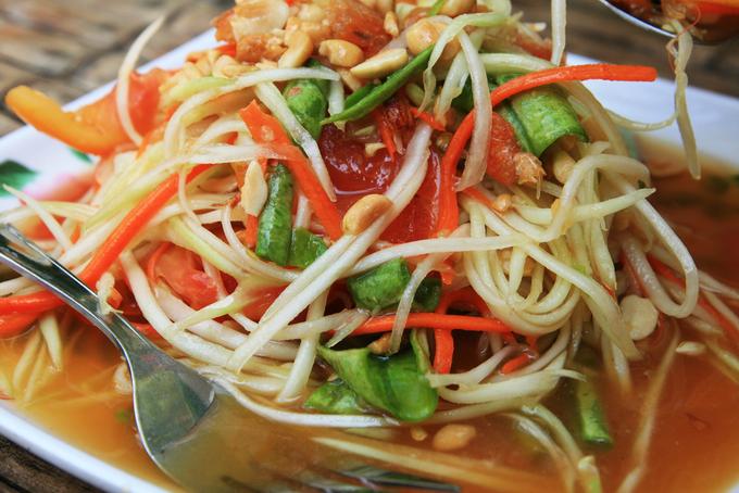 Som Tam (gỏi đu đủ)  Nguyên liệu của món này gồm đu đủ bào sợi, ớt, tôm khô, cà chua, đậu đũa bẻ nhỏ. Tất cả được cho vào cối giã, sau đó thêm cốt chanh, nước mắm, đường thốt nốt rồi trộn cho gia vị thấm đều vào đu đủ. Vị cay đặc trưng của món ăn Thái sẽ khiến bạn cảm thấy kích thích. Giá mỗi phần Som Tam ở các xe đẩy rong chỉ khoảng 40 – 50 baht (khoảng 30.000 - 40.000 đồng). Ảnh: Shutterstock/Tom Grundy.