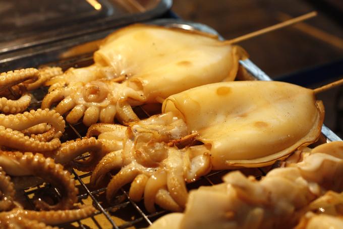 Mực nướng  Theo gió, mùi thơm của mực tươi khi được nướng trực tiếp trên bếp than hoa dễ bay xa. Nếu dạo quanh các khu chợ đêm, bạn đừng quên thử món ăn giòn sần sật này. Để tăng mùi vị của món ăn, người Thái Lan rưới lên mực sau khi nướng nước sốt ngọt và cay. Ngoài ra, các hàng này còn bán đủ loại tôm cá viên chiên, thanh cua... cho bạn tha hồ lựa chọn. Tuỳ theo kích thước mà giá của món ăn sẽ dao động. Ảnh: Hồng Liên.