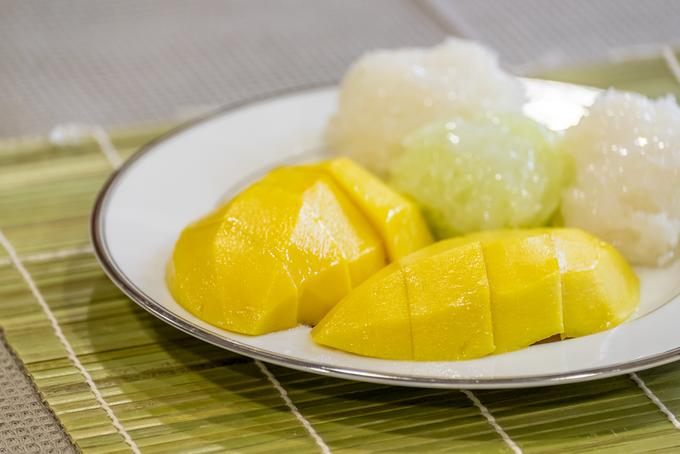 Khao niaow ma muang (xôi xoài)  Ẩm thực Thái Lan còn nổi tiếng với món xôi xoài. Nhiều du khách đùa rằng đến Thái Lan mà không thưởng thức món xôi xoài thì quả là thiếu sót lớn. Hai nguyên liệu chính làm nên món ăn là gạo nếp và xoài tươi. Người Thái thường dùng những quả xoài chín ngọt ăn cùng xôi nếp. Bên trên còn cho thêm chút sữa béo thơm. Giá trung bình 15 baht (hơn 10.000 đồng) một suất ở đường phố. Ảnh: Shutterstock/Mvazt.