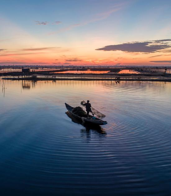 """Đầm Chuồn vào mỗi thời khắc trong ngày mang vẻ đẹp riêng, lúc bình minh có màu cam đỏ hay cam hồng (ảnh), rực sáng trong nắng vàng ban trưa và nhuộm màu tím hồng trong buổi chiều tà.  Đối với các nhiếp ảnh gia, Đầm Chuồn là đề tài để sáng tác ảnh. """"Tờ mờ sáng tôi bấm máy ở Đầm Chuồn với khung cảnh đánh bắt cá quen thuộc, nhưng vẫn bị cuốn hút trước nhịp sống trên thuyền vào lúc bình minh nơi đây"""", tay máy Nông Thanh Toàn, ở Huế, chia sẻ."""