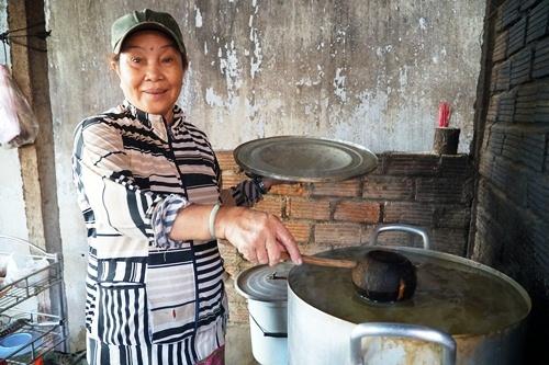 Bà Liên múc don cho khách bằng gáo dừa và gánh thử đôi ui đựng don của mẹ chồng để lại. Ảnh: Phạm Linh.