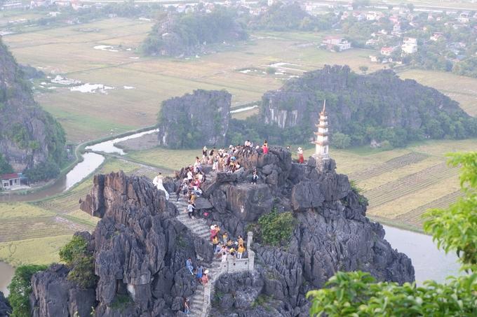 Hang Múa cũng là điểm mà bạn có thể ngắm trọn vẹn Ninh Bình từ trên cao. Giá vé vào cổng 100.000 đồng/người. Bạn phải leo hơn 500 bậc thang để lên đến đỉnh. Từ dưới lên đến ngã ba, rẽ phải là bảo tháp, nơi hút du khách thập phương đến chụp ảnh check-in nên nơi này luôn đông đúc. Bạn phải xếp hàng đợi đến lượt chụp hình. Nếu ngại chen chúc thì có thể để dành lúc sắp về, khi mọi người đã xuống núi bớt thì leo lên cũng không muộn.