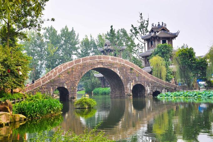 Ngoài những con đường, cầu phủ đầy rêu phong, cổ trấn cũng nổi tiếng với 6 cây bồ đề hơn 800 năm tuổi, trong đó một cây được đặt theo tên của nhà quân sư Gia Cát Lượng. Đến Hoàng Long Khê, du khách còn có thể ghé thăm động Phật, chiến trường cổ hay những ngôi mộ cổ cheo leo trên vách đá. Ảnh: Tony Study Tour.