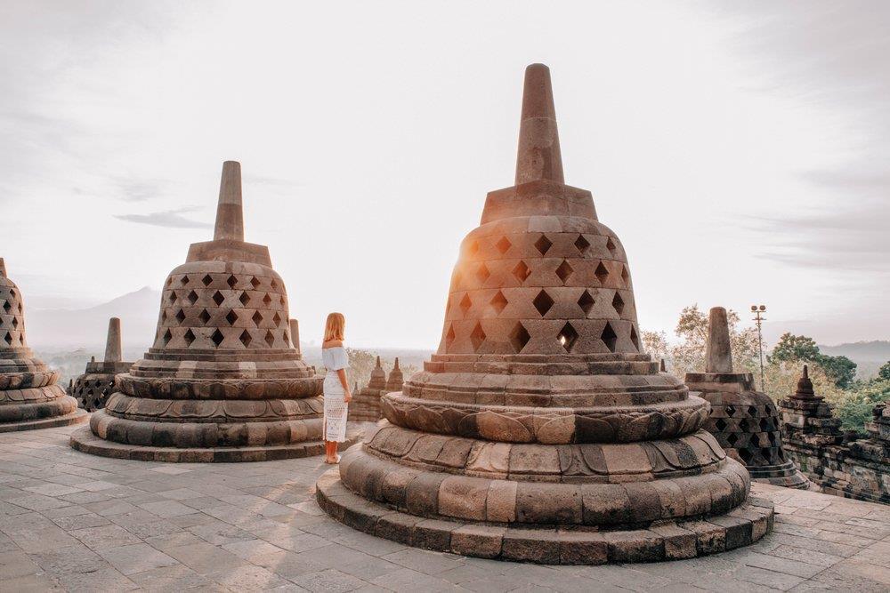 Đối lập với màn đêm huyền bí ở Prambanan là khung cảnh bình minh thơ mộng ở Borobudur - ngôi đền Phật giáo lớn nhất thế giới. Hành trình leo 100 bậc thang dốc đứng để lên tới đỉnh đền khi mặt trời chưa ló rạng, cùng chi phí khoảng 450.000 Rupiah (hơn 700.000 đồng), sẽ được đền đáp xứng đáng khi bạn đứng giữa những bức phù điêu cổ kính, tôn nghiêm, lấp lánh nắng vàng. Ảnh: Lissa Kahayon.