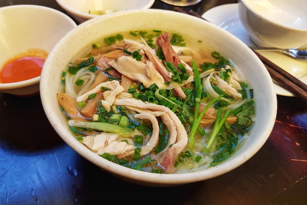 """Sau một buổi sáng dậy sớm, thăm thú Hà Nội, bạn cần ăn bữa trưa đầy đặn để bổ sung năng lượng. Cây viết của Culture Trip gợi ý du khách chọn phở, một món ăn chỉ nghe đã thấy Việt Nam. Phở ở Hà Nội nhiều vô vàn. Tuy nhiên, Piumi cho rằng du khách nên chọn xe ôm để đi ăn cho tiện vì taxi hay bị kẹt ở những con phố đông đúc. """"Phở là món ăn dân tộc của Việt Nam, tạo thành từ nước dùng, bánh phở và thịt. Nếu là người ăn chay, bạn chỉ cần nói 'chay, chay', chủ quán sẽ biết phải làm gì"""", cô hướng dẫn. Ảnh: Shutterstock."""