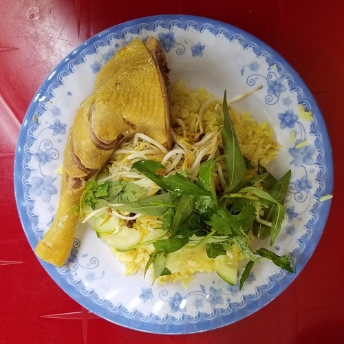 Phần đùi gà chín vàng được xếp cùng cơm, trang trí rau dăm, giá, hành củ muối. Ảnh: Tung Nguyen.