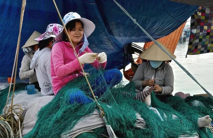 """Trong khi đàn ông ra khơi, phụ nữ ở nhà làm nghề vá lưới thuê để có thu nhập, khoảng 100.000 đồng mỗi ngày công. Với những loại lưới mắt to, đồ nghề chỉ gồm móc lưới bằng nhựa giống chiếc ghim kẹp, con dao nhỏ và cuộn dây. """"Chủ tàu nào thuê tôi cũng nhận, có khi không vá tại cảng mà phải lên thuyền đi cùng họ, lênh đênh trên những con sóng xa bờ"""", một phụ nữ đã làm nghề 20 năm chia sẻ. Ảnh: Jean-noel Chatelain."""