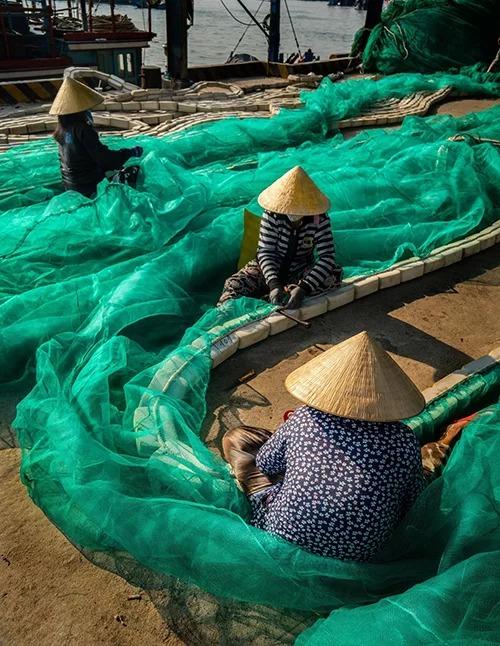 Cảnh vá lưới ở cảng Hòn Rớ thu hút nhiều du khách và những người thích chụp ảnh tìm đến. Ảnh: Phạm Hưng.
