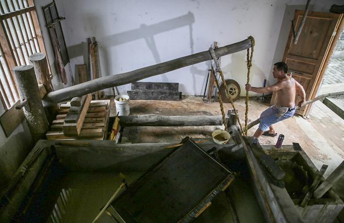 Chồng giấy ướt tiếp tục được chuyển qua công đoạn ép. Li Zhijun đặt chồng giấy dưới những thanh gỗ rồi dùng một hệ thống đòn bẩy để vắt nước.