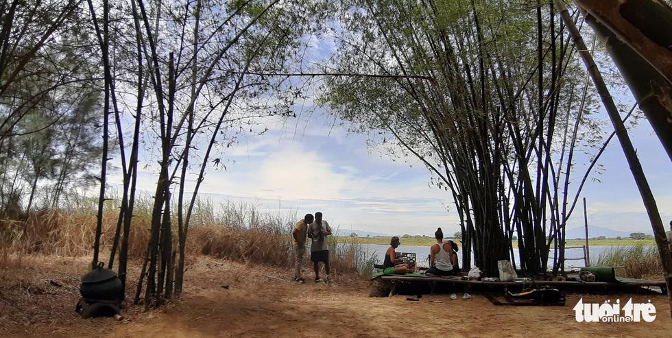 Một gia đình du khách đến tham quan An Nhiên farm ngồi nghỉ mát dưới lũy tre xanh - Ảnh: LÊ TRUNG
