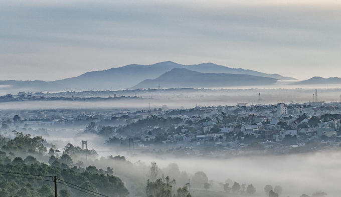 """Một góc thành phố Pleiku đoạn cầu Phan Đình Phùng trong sương mù buổi sáng tháng 6. Anh Hoàng Quốc Vĩnh, một tay máy, cho biết sương hòa quyện với mây từ ngọn Hàm Rồng cao trên 1.000 m tràn xuống thung lũng tạo nên """"cảnh đẹp tựa chốn thần tiên""""."""